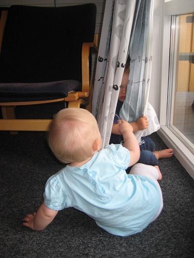 "Elise och Milton leker ""titt ut"" med gardinen."