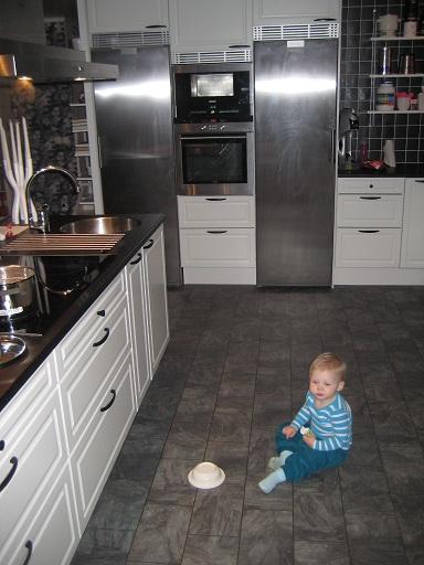 En liten sjuk Elise i vårt stora smutsiga kök.